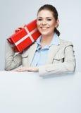 Tenuta rossa sorridente del contenitore di regalo della donna di affari Fotografie Stock Libere da Diritti