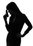 Tenuta sexy della donna dell'agente investigativo che tende la siluetta della pistola Fotografia Stock