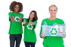 Tenuta sorridente dell'attivista che ricicla scatola Fotografia Stock