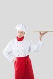 Tenute del cuoco in una mano un vassoio Fotografia Stock