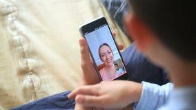 Tenute dell'adolescente del ragazzo una video chiacchierata con una donna su uno smartphone archivi video