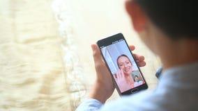 Tenute dell'adolescente del ragazzo una video chiacchierata con una donna su uno smartphone video d archivio