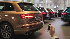Tenute della mano ed usando chiave a distanza per sbloccare 4 automobili Lampeggiamento dei segnali di giro Automobili nuovissime video d archivio