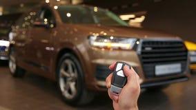 Tenute della mano ed usando chiave a distanza per sbloccare un'automobile Lampeggiamento dei segnali di giro Automobile brandnew  video d archivio