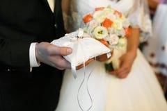 Tenute dello sposo nel suo fedi nuziali del braccio Fotografie Stock Libere da Diritti