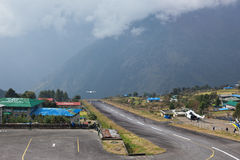 Tenzing-Hillary Airport in Lukla. Airport staff look at one more plane taking off from Tenzing-Hillary Airport - the most dangerous airport in the world. Lukla stock image