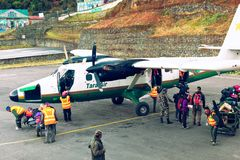 Tenzing-Hillary airport in Lukla. Airport staff unload arrived aircraft of Tara Air - famous nepalese airline provider. Tenzing-Hillary airport, Lukla, Nepal stock photography