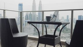 Two chairs at terrace. Teo chairs and a table with cup of coffee and open laptop at terrace with beautiful view over the city. Luxury apartment balcony and stock footage