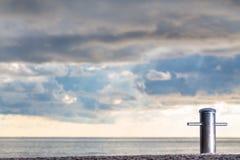 Teowy metalu cleat dla statków i jachtów przy zmierzch dramatycznymi chmurami Zdjęcie Stock