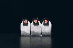 Tepåsar på en mörk bakgrund står i rad Royaltyfri Fotografi