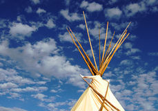 Tepee and Clouds. Behind a real tepee, clouds appear as smoke signals blowing across the New Mexican sky Stock Photo