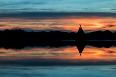 Tepee Lake Reflection. Tepee on a lake shore with the water giving a wonderful reflection of the sunset Stock Photo