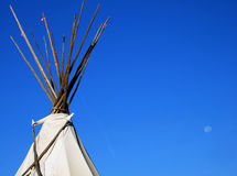 Tepee and Moon. Native American Tepee in Santa Fe, New Mexico, against a clear blue sky with a fading moon Royalty Free Stock Photo