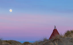 Tepee Moonlight. Tepee on a beach sand dune, with a bright moon in the dawn sky Stock Photo
