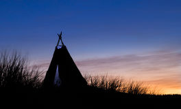 Tepee Morning Light. Tepee tent on a hill with dawn light behind it Royalty Free Stock Image