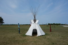 Tepee and totem poles Stock Photography