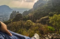 Foot of man contemplating the horizon at the top of Tepozteco Hill in Tepoztlan. Beautiful mountainous view. Tepozteco hill. Archaeological site located in the stock images