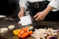 Teppanyaki Chef Cooking. A Teppanyaki chef cooking vegetables on grill table Royalty Free Stock Photos