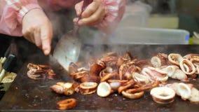 Teppanyaki-Koch, der den Kalmar, Kopffüßer mit Soße auf heißer Wannenplatte schneidet stock video footage