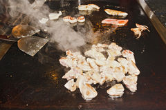 Teppanyaki Mix. Teppanyaki japanese cousing in an asian restaurant raw fish meat cooking with smoke for entertainment of customers Stock Photography