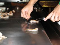 Teppanyaki Style Cooking. Teppanyaki chef cutting and cooking shrimp on the table grill stock image