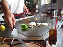 Teppanyaki Style Cooking. Teppanyaki chef cooking chicken and vegetables on the table grill Royalty Free Stock Photo