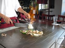 Teppanyaki Style Cooking. Teppanyaki chef cooking vegetables on the table grill Stock Photo