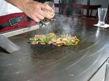 Teppanyaki Style Cooking. Teppanyaki chef cooking vegetables on the table grill Royalty Free Stock Images