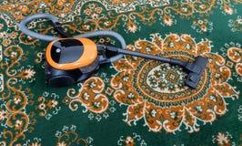 Teppich, der zu Hause mit Staubsauger Staub saugt stockfotos