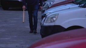 Teppista arrogante con la mazza da baseball che va distruggere e rubare le automobili nel parcheggio archivi video