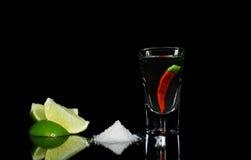 Tequila με το τσίλι στη μαύρη ανασκόπηση στοκ φωτογραφία με δικαίωμα ελεύθερης χρήσης