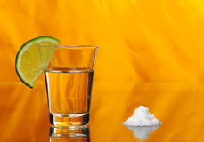 Tequila. Shot with a half a slice of lime on the glass and a pile of salt by the side on orange background (Selective Focus Stock Photo
