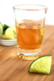 Tequila. Shooter glass with tequila and lime on wood cutboard Stock Photos