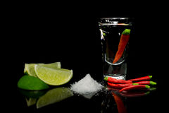 Tequila with chili on black background Royalty Free Stock Images