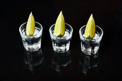 Tequila com cal no fundo preto Imagens de Stock