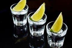 Tequila com cal no fundo preto Fotografia de Stock