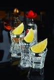 Tequila com cal no fundo preto Fotos de Stock