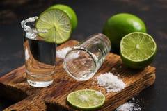 Tequila con la rebanada de la cal y sal en una tabla de cortar Una pila borracha de tequila está vacía en una tabla de cortar Foc imagen de archivo