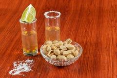 Tequila de oro con el limón, pistachos, cacahuate, y sal Bebidas, licor fotografía de archivo libre de regalías