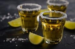 Tequila del oro con el borde de la cal y de la sal en piedra oscura o fondo concreto Imagenes de archivo