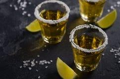 Tequila del oro con el borde de la cal y de la sal en piedra oscura o fondo concreto Imagen de archivo libre de regalías