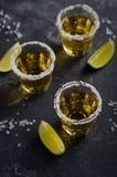 Tequila del oro con el borde de la cal y de la sal en piedra oscura o fondo concreto Imágenes de archivo libres de regalías