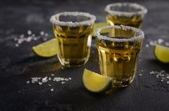 Tequila del oro con el borde de la cal y de la sal en piedra oscura o fondo concreto Imagen de archivo