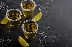 Tequila del oro con el borde de la cal y de la sal en piedra oscura o fondo concreto Foto de archivo