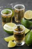 Tequila del oro en un vaso de medida de cristal con cierre de la sal y de la cal para arriba en un fondo concreto negro Barra Beb imagenes de archivo