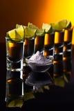 Tequila do ouro em um fundo reflexivo preto Imagens de Stock