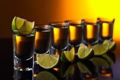 Tequila do ouro em um fundo reflexivo preto Fotos de Stock