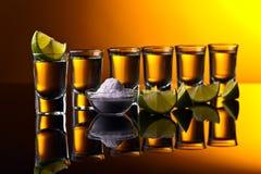 Tequila do ouro em um fundo reflexivo preto Foto de Stock Royalty Free
