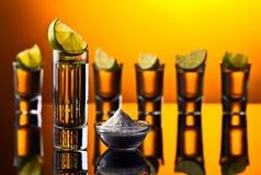 Tequila do ouro em um fundo reflexivo preto Imagens de Stock Royalty Free