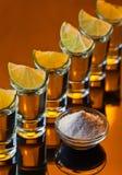 Tequila do ouro em um fundo reflexivo preto Imagem de Stock